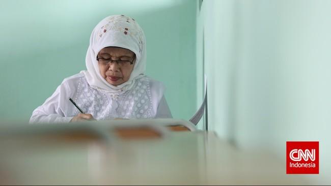 Seorang ibu mengikuti ujian nasional kesetaraan paket B di SMA Negeri 80, Jakarta Utara, Senin, 4 Mei 2015. Ujian Nasional Paket B diikuti oleh 387 peserta dari 16 pusat kegiatan belajar masyarakat (PKBM) dari tiga kecamatan yakni Penjaringan, Pademangan dan Tanjung Priok. (CNN Indonesia/Safir Makki)