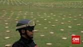 Petugas menjaga 2,1 ton ganja yang 'dipamerkan' Direktorat Tindak Pidana Narkoba Badan Reserse Kriminal di Lapangan Bhayangkara Mabes Polri, Jakarta, Senin (11/5). Ganja-ganja ini dibawa jaringan pengedar dari Aceh ke Jakarta. (CNN Indonesia/Adhi Wicaksono)
