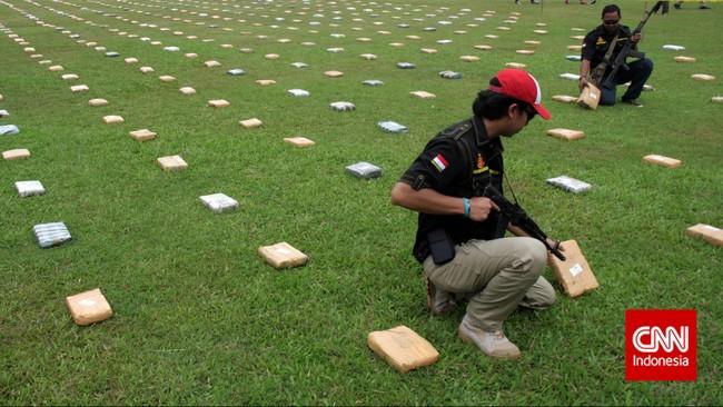Petugas memeriksa 2,1 ton ganja yang 'dipamerkan' Direktorat Tindak Pidana Narkoba Badan Reserse Kriminal di Lapangan Bhayangkara Mabes Polri, Jakarta, Senin (11/5). Dalam menyita ganja-ganja ini dari jaringan pengedar Aceh, polisi menangkap empat orang di Jakarta Selatan. (CNN Indonesia/Adhi Wicaksono)