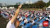 Instruktur yoga kembali menunjukkan contoh gerakan yang diikuti oleh ribuan peserta yoga massal yang memadati kawasan Monas, Jakarta Pusat.