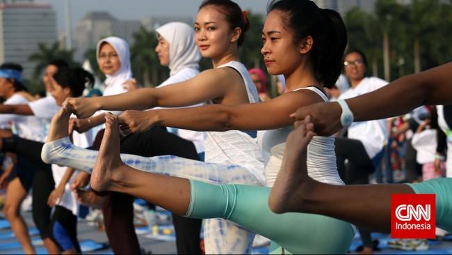 Peserta yoga massal di kawasan Monas, Jakarta Pusat melakukan peregangan kaki mengikuti petunjuk instruktur.