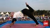 Instruktur yoga memberikan contoh gerakan yang harus diikuti oleh para peserta yoga massal di kawasan Monas, Jakarta Pusat tadi pagi.