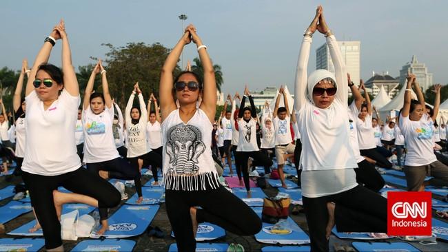 Teriknya sinar matahari tidak menghalangi semangat para peserta yoga massal untuk memecahkan rekor MURI. Kacamata hitam menjadi solusi.