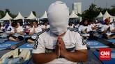 Pria yang menjadi peserta yoga massal ini menutupi kepalanya dengan handuk untuk meningkatkan konsentrasi meditasi.