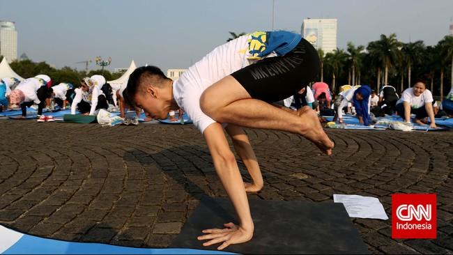 Peserta yoga massal di Monas, Jakarta memperagakan keahliannya mengangkat tubuhnya dengan dua tangan.