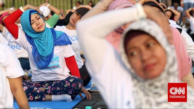 Para peserta yoga massal mengikuti gerakan pendinginan yang ditunjukkan oleh instruktur di sesi akhir kegiatan yoga massal di Monas, Jakarta Pusat.