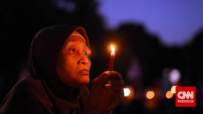 Seorang ibu yang ikut serta dalam peringatan 17 tahun memperingati reformasi yang dilakukan oleh gabungan relawan Jokowi di Lapangan Tugu Proklamasi, Jakarta, Kamis, 21 Mei 2015. (CNNIndonesia/Adhi Wicaksono)