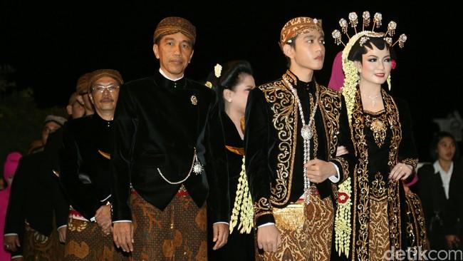 Di belakangnya, Joko Widodo didampingi oleh Iriana berjalan mengenakan pakaian berwarna senada dengan bawahan kain truntum. Begitu pula dengan kedua orang tua Selvi yang ada di belakang sang Presiden. (Detikcom/Agung Pambudhy)