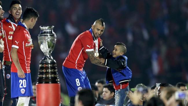 Arturo Vidal hendak menggendong putranya sebelum timnya diserahkan trofi Copa America 2015. Di partai final Chile mengalahkan timnas Argentina, 4 Juli 2015. (REUTERS/Jorge Adorno)