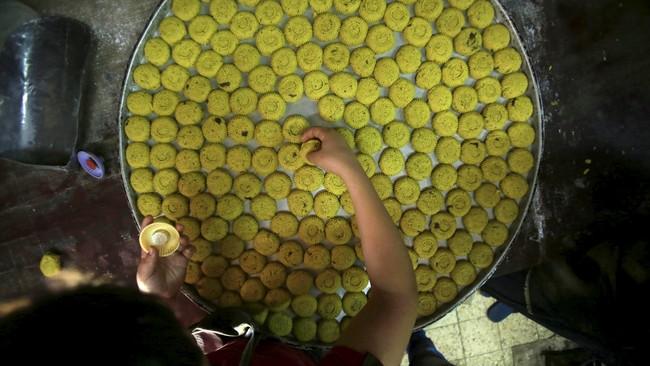Di Tepi Barat, warga Palestina menyajikan satu jenis kue tradisional lebaran yang dipersiapkan secara khusus. (Reuters/Abed Omar Qusini)