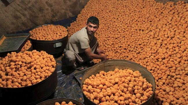 Seorang pekerja mempersiapkan makanan manis khusus yang akan banyak dibeli warga Jalalabad, Afghanistan sebagai panganan di hari Lebaran. (Reuters/Parwiz)