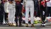 Sebelum dimulai, para pebalap meletakkan helm-helm mereka di aspal Sirkuit Hungaroring dan mengheningkan cipta atas wafatnya Jules Bianchi setelah sembilan bulan koma. (REUTERS/Laszlo Balogh)