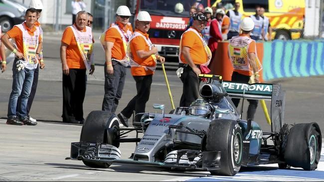 Pebalap Mercedes Nico Rosberg pelan-pelan kembali ke pit stop setelah ban mobilnya pecah usai bertabrakan dengan mobil pebalap tim Red Bull Daniel Ricciardo.(REUTERS/Ronald Zak)