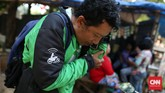 Seorang pengemudi mitra Gojek menerima panggilan telepon dari calon penumpang yang memesan layanan ini di kawasan Jakarta Timur, Selasa, 4 Agustus 2015. (CNN Indonesia/Safir Makki)