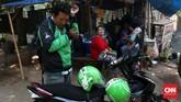 Setiap pengemudi mitra Gojek wajib membawa dua helm untuk dirinya dan penumpang karena mengutamakan keselamatan berkendara. Selain helm, pengemudi juga wajib memberikan masker dan sarung kepala untuk penumpangnya. (CNN Indonesia/Safir Makki)