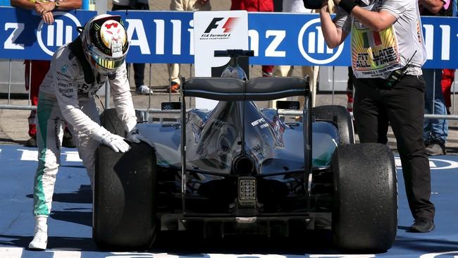 Kemenangan Hamilton sempat terancam karena tekanan ban kiri belakangnya tidak sesuai aturan. Pebalap Inggris itu lalu merayakan kemenangannya dengan memegang ban kiri tersebut. (Action Images/Livepic/Hoch Zwei)