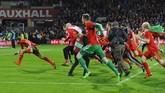 Gareth Bale (kiri) bersama rekan-rekannya di timnas Wales merayakan untuk kali pertama negara itu lolos ke putaran final kejuaraan sepak bola internasional mayor. Wales berhasil meraih satu tiket putaran final Piala Eropa 2016 yang berlangsung di Perancis. (Reuters / Rebecca Naden)
