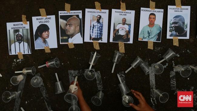 Aktivis keagamaan dan jaringan buruh migran memasang gambar terpidana mati dan sejumlah lilin di depan Istana Merdeka, Jakarta, Selasa, 28 April 2015. Mereka mengajak masyarakat menolak keputusan Jokowi mengeksekusi terpidana mati. (CNN Indonesia/Safir Makki)