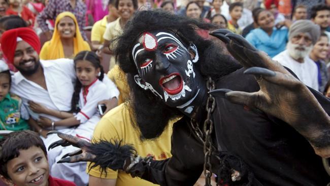 Seorang seniman menyamar seperti setan dalam sebuah drama keagamaan pada perayaan Festival Dussehra di Chandigarh, India. (Reuters Ajay Verma)