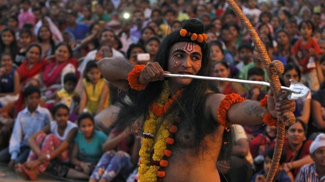 Seorang seniman berpakaian menyerupai Dewa Hindu Rama dalam sebuah drama keagamaan selama festival Dussehra di Chandigarh, India, pada 22 Oktober 2015. (Reuters/Ajay Verma)