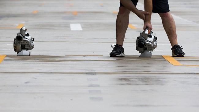 Seperti halnya tim Merceders dan Williams, kru dari tim Red Bull pun berusaha mengeringkan lintasan di pit tim balapnya usai hujan. (REUTERS/Adrees Latif)