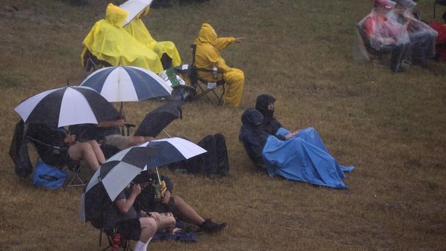 Para penggemar formula satu (F1) ini bertahan di pinggir sirkuit menantikan latihan bebas II dilanjutkan. Nyatanya Latihan Bebas II dibatalkan akibat hujan deras tersebut. (REUTERS/Adrees Latif)