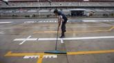 Ketika hujan reda, seorang kru pit tim Williams mencoba menggiring air keluar dari tempat parkir mobil balap. (REUTERS/Adrees Latif)