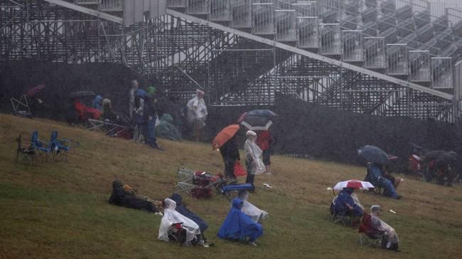 Para penggemar menggunakan payung untuk melindungi tubuh mereka dari basah akibat derasnya hujan saat menyaksikan Latihan Bebas II GP Amerika, di Austin, Texas, 23 Oktober 2014. (REUTERS/Adrees Latif)