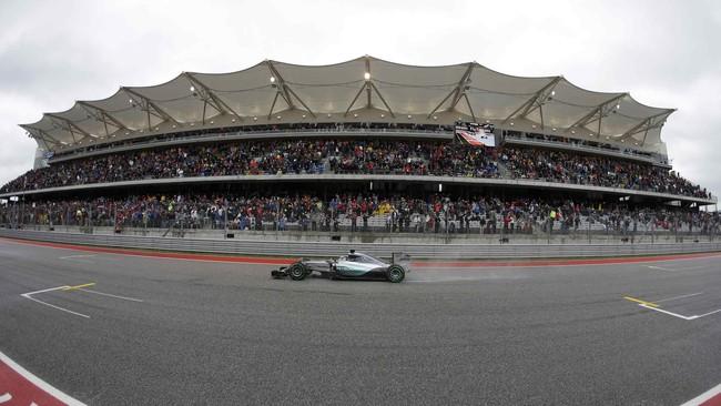 Mobil Hamilton melewati tribun grandstand yang dipenuhi oleh ribuan penonton. Mereka tahu bahwa jika memastikan keunggulan tujuh angka dari Sebastian Vettel pada balapan kali ini, Hamilton akan keluar menjadi juara dunia. (REUTERS/Darron Cummings)
