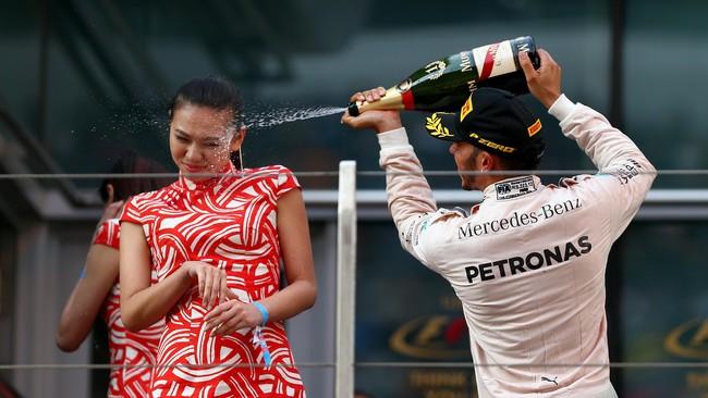 Lewis Hamilton sempat mendapat sorotan ketika ia menyemprot seorang gadis panggung seusai juara di GP China. Aksi Hamilton ini dianggap seksis dan ia menerima kecaman. (Getty Images/Dan Istitene)