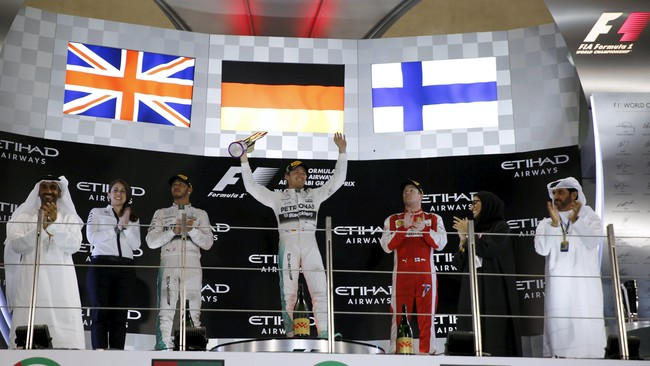 Pebalap Mercedes Nico Rosberg (tengah) merayakan kemenangan dirinya di atas podium pertama seri grand prix Formula 1 (F1) di sirkuit Yas Marina, Abu Dhabi, 29 November 2015. (REUTERS/Roula Rouhana)