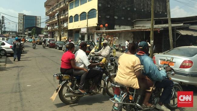 Sama seperti di Jakarta, penduduk Kamerun juga sering mengendarai sepeda motor bertiga. Tapi bedanya, tak akan ada polisi yang menilang pengendara Kamerun. (Foto: CNN Indonesia/Christina Andhika Setyanti)