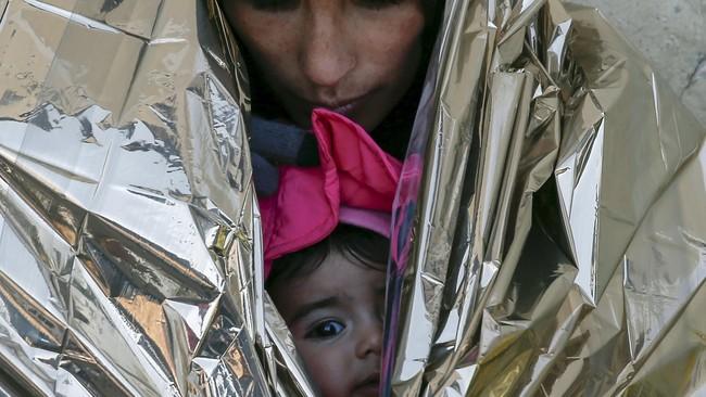 Pengungsi menyelimuti anak mereka di tengah musim dingin menggigit di Serbia. Musim dingin Eropa dikhawatirkan mengancam nyawa para pencari suaka, terutama anak-anak. (Reuters/Marko Djurica)