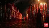 Petugas kelenteng membakar hio raksasa milik umat di Kelenteng Dewi Kwan Im. Ratusan hio milik umat ini dibakar secara bersamaan menjelang detik-detik pergantian tahun baru. (CNN Indonesia/Safir Makki)