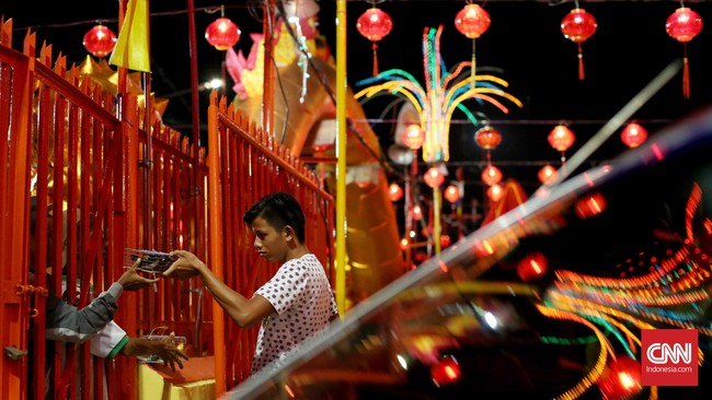 Seorang umat membeli burung di Kelenteng. Burung-burung ini akan diterbangkan usai beribadah sebagai simbol melepaskan diri dari bala atau kemalangan. (CNN Indonesia/Safir Makki)