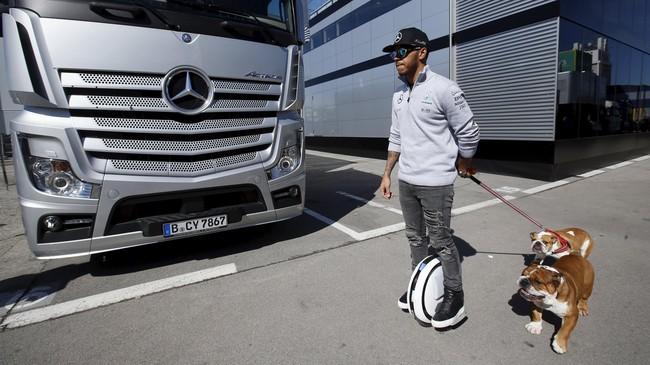 Juara dunia musim lalu, Lewis Hamilton, terlihat santai mengajak anjingnya berjalan-jalan dengan 'sepeda roda satu' di blok parkir tim Mercedes. (Reuters/Albert Gea)