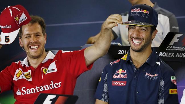 Daniel Ricciardo (kanan) tertawa ketika mendengar pertanyaan wartawan mengenai spekulasi dirinya akan bergabung dengan tim Ferrari dalam jumpa pers jelang musim balap 2016 di Melbourne, Australia, Kamis (17/3). Pebalap Ferrari Sebastian Vettel yang duduk di sebelahnya pun terbersit ide usil mendengarnya. (Reuters/Brandon Malone)
