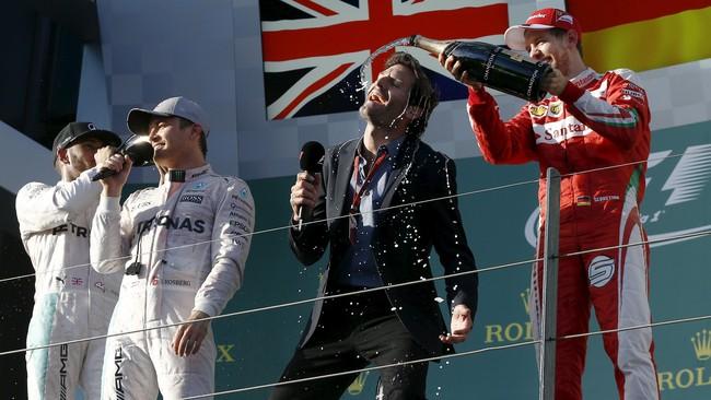 Sebastian Vettel yang merebut podium tiga bergurau dengan mantan rekan setimnya di Red Bull, Mark Webber. Vettel sempat berkata bahwa ingin Webber kembali menjadi rekannya. Webber sendiri kini telah beralih menjadi pebalap Le Mans. (REUTERS/Jason Reed)