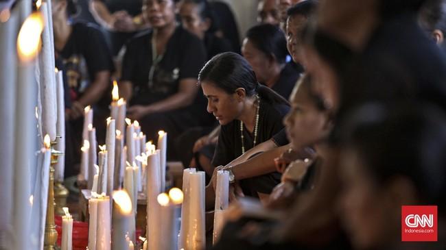 Peziarah menyalakan lilin di depan Kapela Tuhan Ma sambil melantunkan doa-doa di hadapan patung Mater Dolorosa. (CNN Indonesia/Adhi Wicaksono)