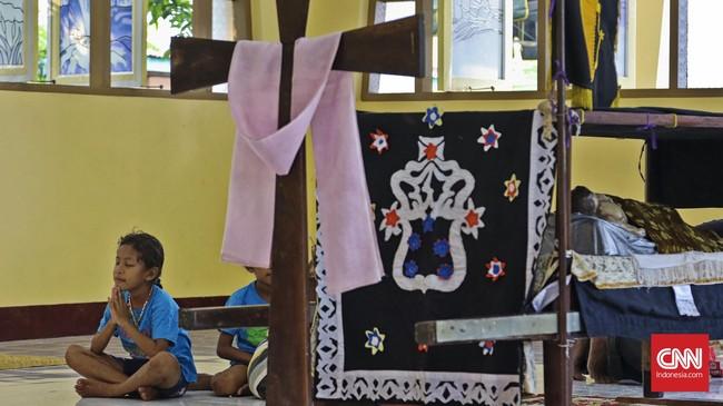 Peziarah berdoa di samping Patung Jenazah Yesus dalam Keranda di Kapel Tuan Senhor, Wure, Adonara, NTT,Kamis (23/3). (CNN Indonesia/Adhi Wicaksono)