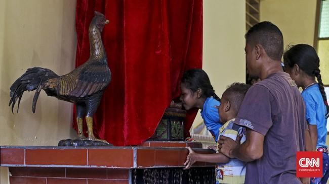 Peziarah mencium kaki Patung Tuhan Berdiri di Kapel Tuan Senhor, Wure, Adonara, NTT, Kamis (23/3). Di Kapel Wure itu berdiri tegak sebuah arca Yesus (orangLarantuka menyebutnya Tuan Bedir) sambil memegang seekor ayam jantan. (CNN Indonesia/Adhi Wicaksono)