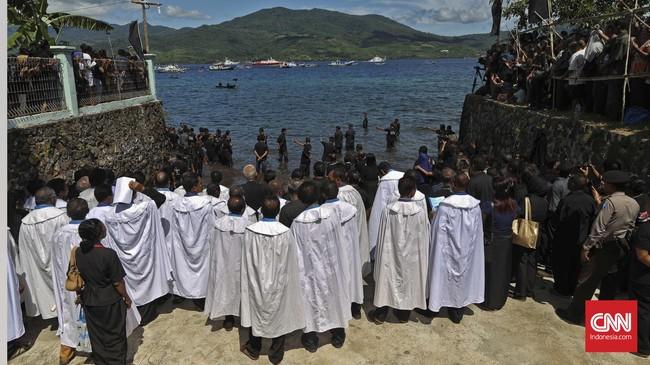 Confreria menunggu kedatangan perahu pembawa Tuhan Meninu usai arak-arakan patung bayi Yesus selesai digelar. (CNN Indonesia/Adhi Wicaksono)