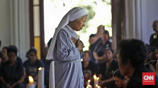 Seorang biarawati menuju pintu kapela usai mencium Tuhan Ma. Antrean peziarah untuk upacara ini terjadi hingga malamhari pada Kamis Putih. (CNN Indonesia/Adhi Wicaksono)