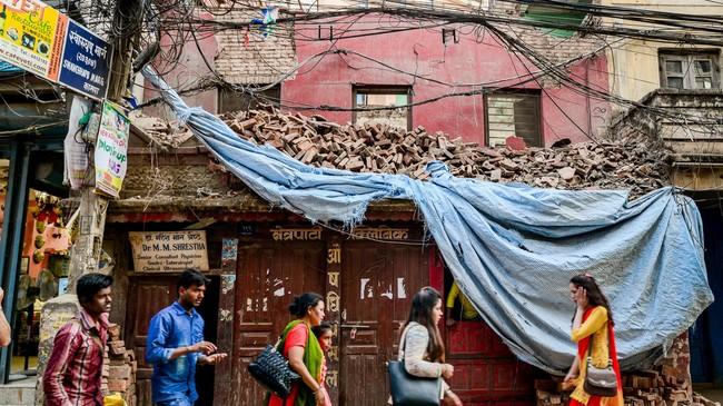 Warga Kathmandu bersiapmemulai aktivitas saat melintasi reruntuhan bangunan di kawasan Thamel. Banyak warga masih berduka lantaran anggota keluarganya tak ditemukan lagi jejaknya usai gempa. (Reynold Sumayku)