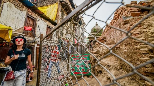 Seorang turis melewati gang kecil di tepi reruntuhan bangunan bersejarah di Durbar Square, Kathmandu. Setelah mengumpulkan data, mengkaji, serta melakukan perencanaan, secara resmi pemerintah Nepal baru akan memulai rekonstruksi pada 25 April 2016, tepat setahun setelah gempa bumi terjadi. (Reynold Sumayku)