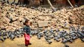 <p>Seorang anak berdiri sehabis memberi makan sekumpulan burung merpati di pelataran Kuil Jagannath yang dipenuhi batu bata dari reruntuhan bencana gempa bumi di kawasan Durbar Square, Kathmandu. (Reynold Sumayku)</p>