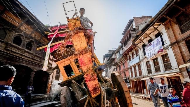 Seorang remaja menaiki chariot (kereta upacara tradisional) berbahan kayu yang terperosok ke sebuah lubang di Bhaktapur. Sebagai 'Ibu Kota budaya Nepal', Bhaktapur mengalami banyak tantangan dalam merekonstruksi bangunan-bangunan cagar budayanya. (Reynold Sumayku)