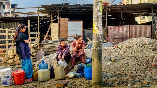 Sejumlah perempuan menanti kedatangan truk pembawa tangki air bersih ke permukiman sementara mereka di tepi ruas jalan Kathmandu-Bhaktapur. Kekurangan air menjadi masalah besar di perkotaan setelah sejumlah infrastruktur ikut hancur oleh gempa bumi. Truk air pun hanya datang seminggu sekali. (Reynold Sumayku)