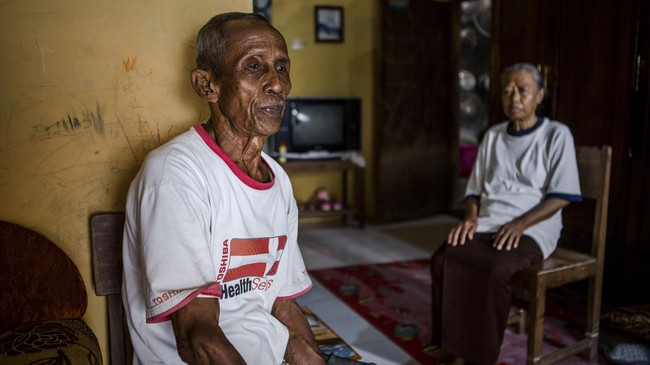 Sukar bersama istrinya Ribut di rumah yangmereka tinggali tak jauh dari lokasi di mana diyakni dimakamkan korban tragedi 1965 di Hutan Plumbon, Wonosari, Semarang, Jateng.(Getty Images/Ulet Ifansasti)
