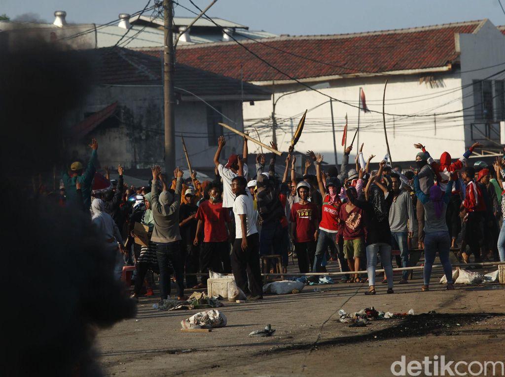 Warga melawan dengan membawa bambu, membakar ban, dan merusak mobil.